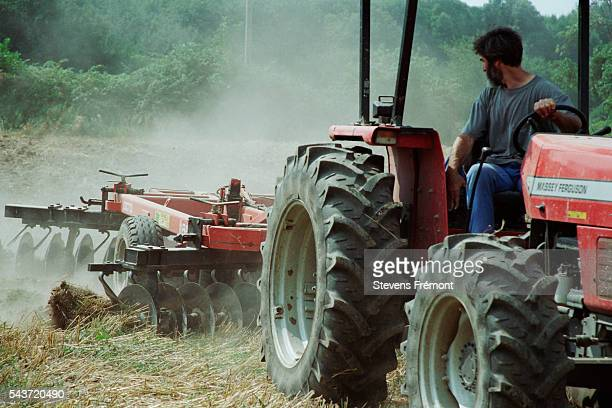 After the harvest a farmer works the land to overturn the culm   Location Courdemanche France