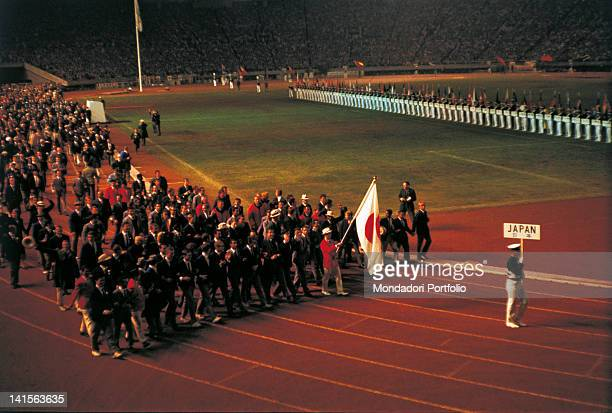 After the Japanese flag the athletes of all nations in a mixture of colours and uniforms are marching on the track of the National Olympic Stadium...