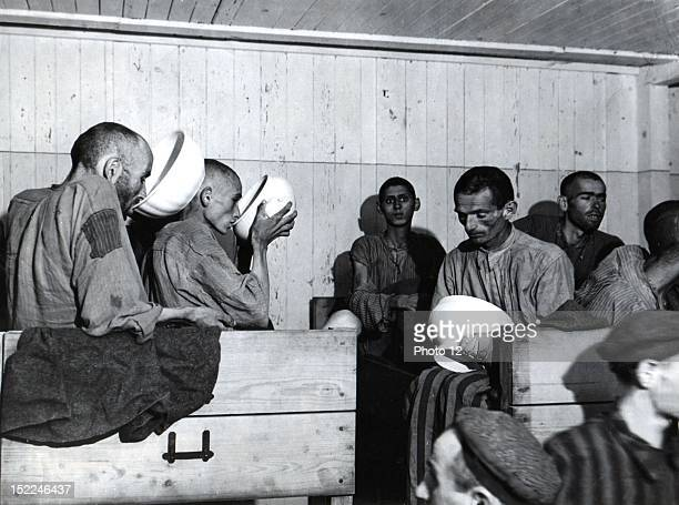 After the liberation by members of the 80th Division 3rd US Army these undernourished inmates drink liquids They are too weak to eat soldid foods at...