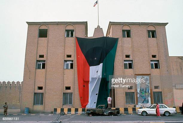 After the liberation of Kuwait a building wears a huge version of the national flag A smashed mosaic probably of Saddam is at bottom right