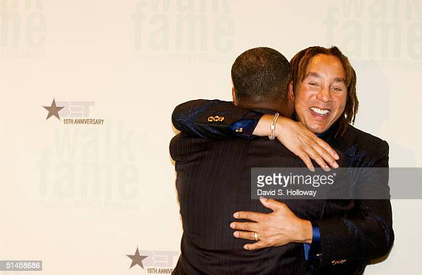 After the performance singer Smokey Robinson hugs his friend Donnie Simpson the host of Black Entertainment Television's 10th Anniversary Walk of...