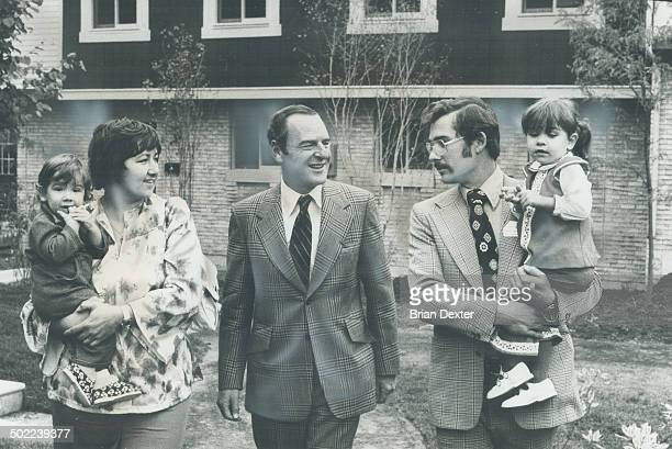 After the ribboncutting Urban affairs Minister Barney Danson chats with Jim and Chris Verrall holding their children in front of their new townhouse...