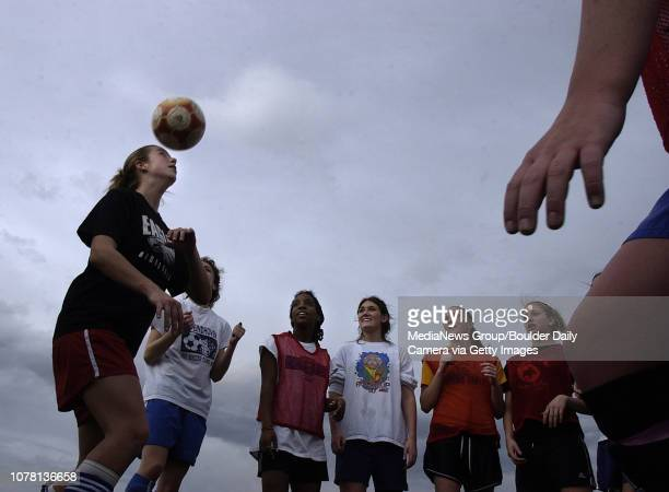 After the team gathered in a circle Samantha Ford left Broomfield High School keeps the ball in the air while passing it to another teammate for a...