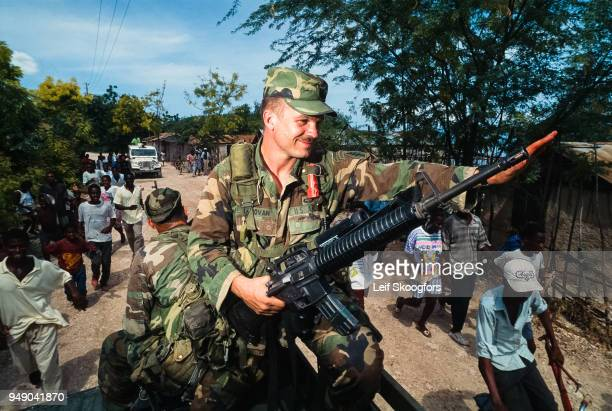 After the US invasion of Haiti an unidentified US Special Forces Captain waves to citizens who run alongside his vehicle Miragoane Haiti 1994