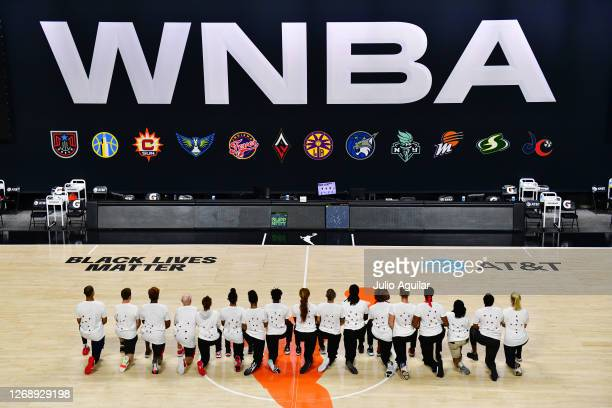 After the WNBA announcement of the postponed games for the evening, the Washington Mystics each wear white T-shirts with seven bullets on the back...