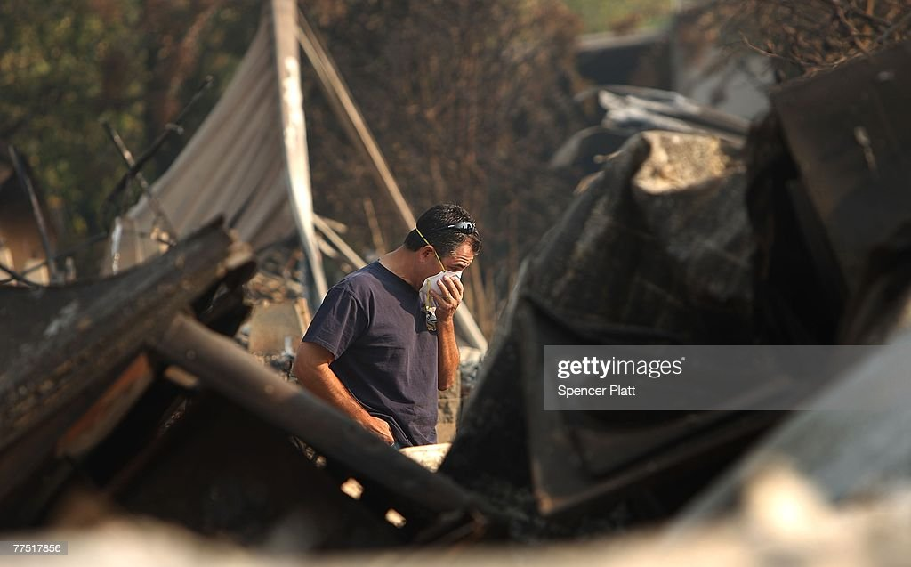 After traveling on back roads to evade police checkpoints, Glenn Torrez looks through the remains of his parents mobile home which was destroyed, with much of the park, by a wildfire October 26, 2007 in Fallbrook, California. With improving weather conditions firefighters continued to make progress against the wildfires in California. The fires caused the largest mass evacuation in California's history, burning nearly 500,000 acres, leaving a heavy toll on the county's agricultural industry and impacting an estimated cost to the state of one billion dollars. Roughly 20,000 avocado trees in the Fallbrook and De Luz areas were destroyed with a range of commodities, from oranges to eggs and even commercial flowers.