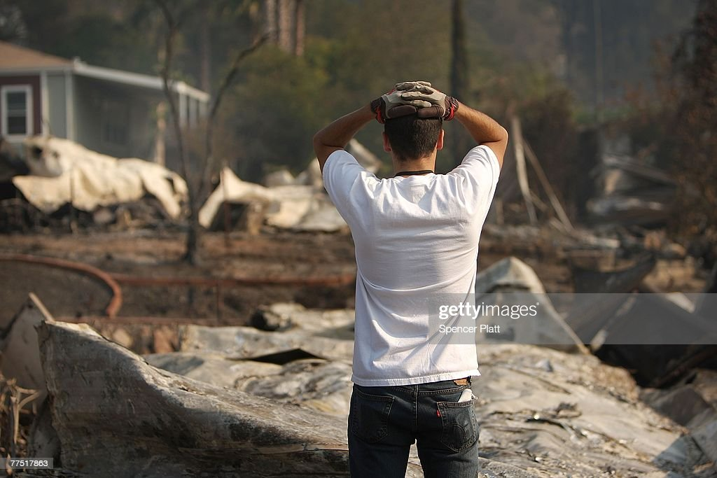 After traveling on back roads to evade police checkpoints, Nolan Torrez looks at the burned remains of his grandparent's mobile home October 26, 2007 in Fallbrook, California. The home was part of a mobile home park destroyed by the wildfires this week in California. With improving weather conditions firefighters continued to make progress against the wildfires. The California fires caused the largest mass evacuation in state's history, burning nearly 500,000 acres, leaving a heavy toll on the county's agricultural industry and impacting an estimated cost to the state of one billion dollars. Roughly 20,000 avocado trees in the Fallbrook and De Luz areas were destroyed with a range of commodities, from oranges to eggs and even commercial flowers.