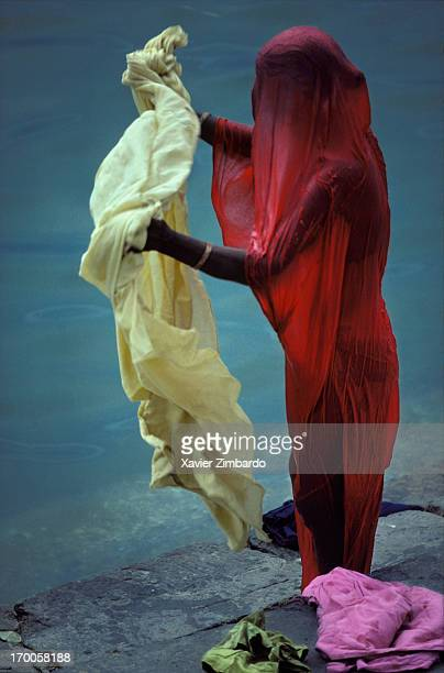 After washing her yellow sari to go and pray in temples this young woman gently shakes the fabric in the wind to speed its drying on July 27 1982...
