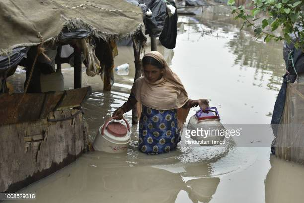 After water level of Yamuna River rose a local residents Rekha Rani is seen taking out her belongings from her submerged house at opposite Rajghat...