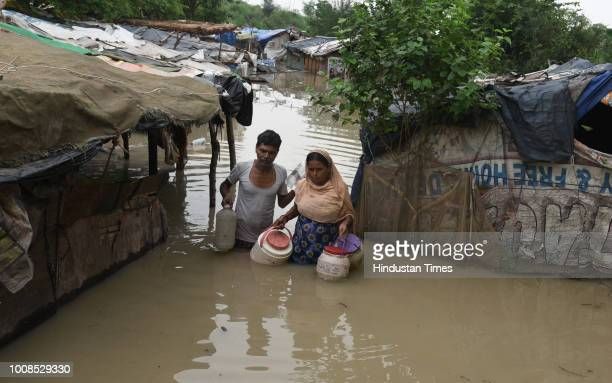 After water level of Yamuna River rose local residents Rekha Rani along with Dinesh Ram are seen taking out their belongings from their submerged...