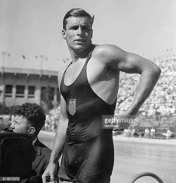 After winning gold in the 400-meter freestyle event at the Los Angeles Olympic Games, Buster Crabbe of the United States loosens up his tank suit....