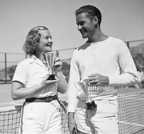 After Winning Mixed Doubles Irene Biller and her partner Errol Flynn with the trophies they won in taking the mixed doubles at the Movie Tennis...