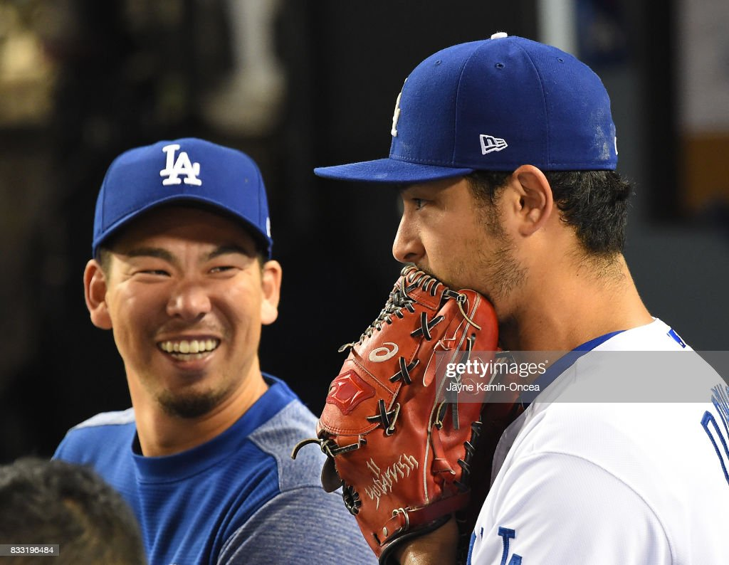 After Yu Darvish #21 of the Los Angeles Dodgers was pulled before the start of the seventh inning, he talks with Kenta Maeda #18 in the dugout in the game against the Chicago White Sox at Dodger Stadium on August 16, 2017 in Los Angeles, California.