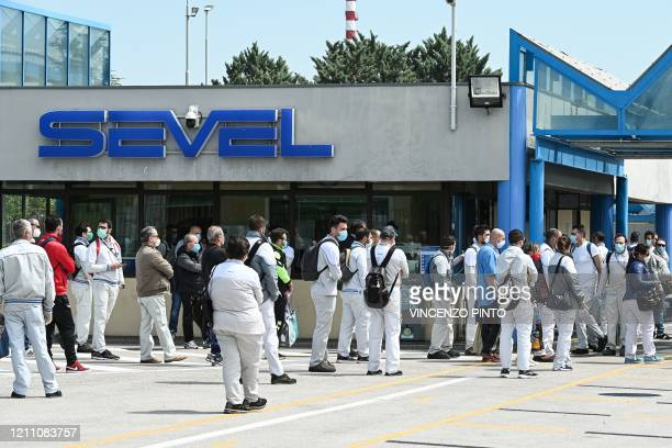Afternoon shift employees line up to go through security and health procedures at the entrance of the Fiat Chrysler Automobiles PSA Group car factory...