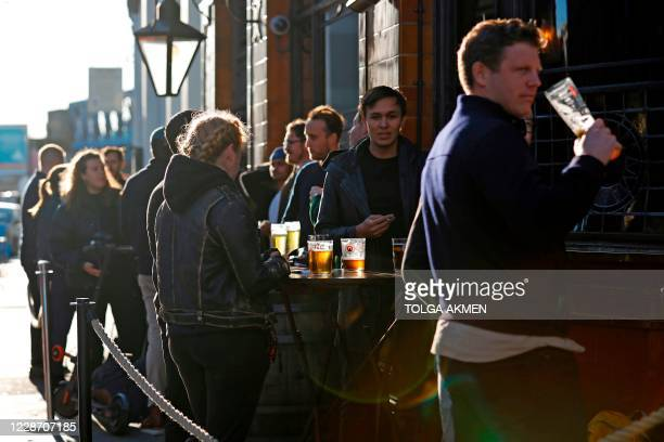 After-work drinkers enjoy a pint outside a pub in Borough Market, in London on September 25 as new earlier closing times for pubs and bars in England...