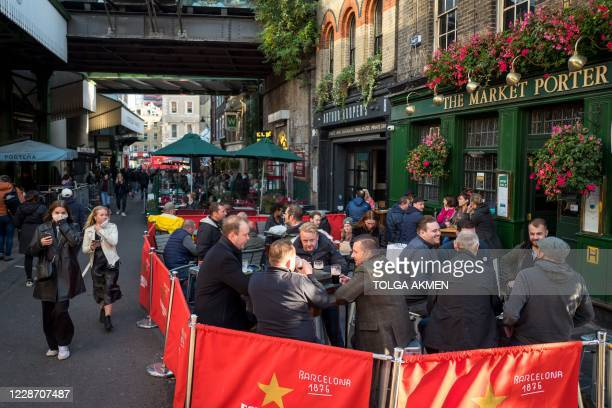 Afterwork drinkers enjoy a pint outside The Market Porter pub in Borough Market in London on September 25 as new earlier closing times for pubs and...