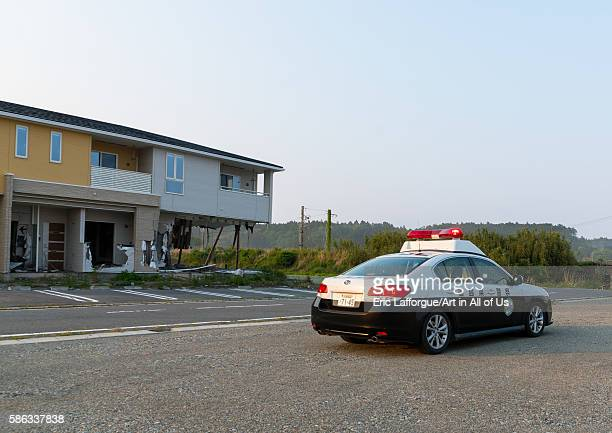 Afukushima police car in front of a house destroyed by the 2011 earthquake and tsunami five years after fukushima prefecture tomioka Japan on May 22...