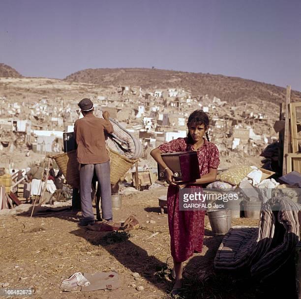 Agadir Earthquake Agadir mars 1960 Une fille portant un poste de radio devant un homme chargeant un matelas sur un âne dans la ville détruite par un...