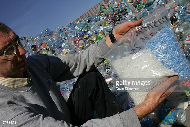 Against a background of thousands of plastic bottles day shift manager Gherman Botrian displays two types of plastics chips one made from blue...