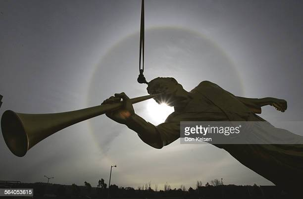 Against a solar halo a golden figure of angel Moroni with trumpet waits to be placed atop the spire of the Newport Beach Temple thursday morning The...