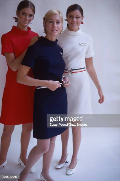 Against a white backdrop a trio of American Airlines air stewardesses help each other into their uniforms September 1967 The photo was taken as part...