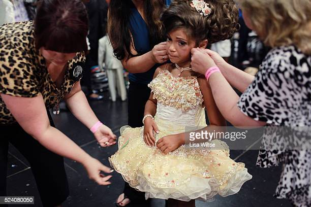 MB age 8 gets help from her Grandmother to put on the final touches of hair spray and adjusts her costume before she goes on stage during the Darling...