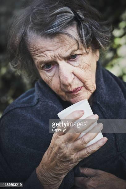 leeftijd dakloze vrouw smeekt, op zoek zielig - bloedvat stockfoto's en -beelden