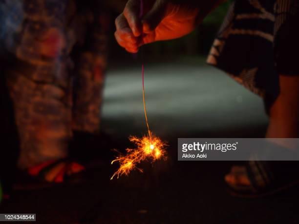 Aged woman And young girl playing Hanabi ( fireworks )