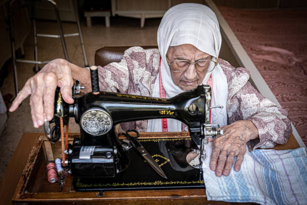 Aged woman working at the sewing machine