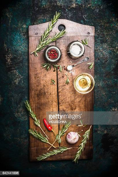 Aged wooden cutting board with herbs and spices on dark vintage background, top view