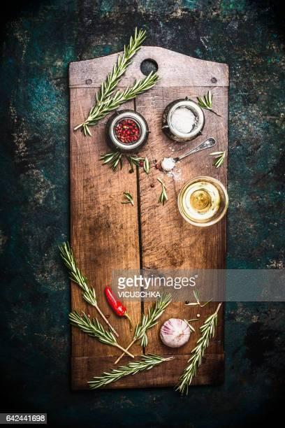 aged wooden cutting board with herbs and spices on dark vintage background, top view - schneidebrett stock-fotos und bilder