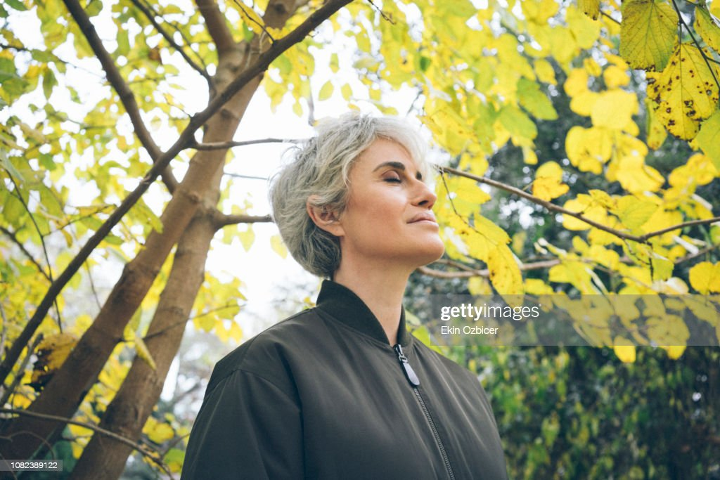 Ageless woman in a park : Stock-Foto