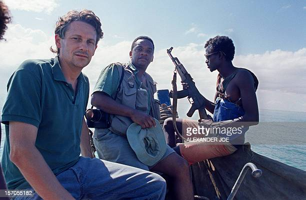 Agence France Presse journalist Michel Sailhan and photojournalist Alexander Joe ride October 1989 in a boat next to a rebel militiaman belonging to...