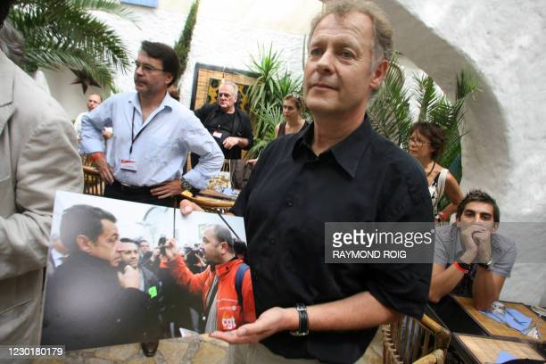 Agence France Presse photographer Eric Feferberg poses with his picture of French President Nicolas Sarkozy and a CGT trade union representative, on...