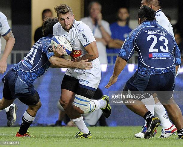 Agen's Benjamin Petre vies with Montpellier's Thomas Combezou and Vincent Pelo during the French Top 14 rugby union match Montpellier vs Agen on...
