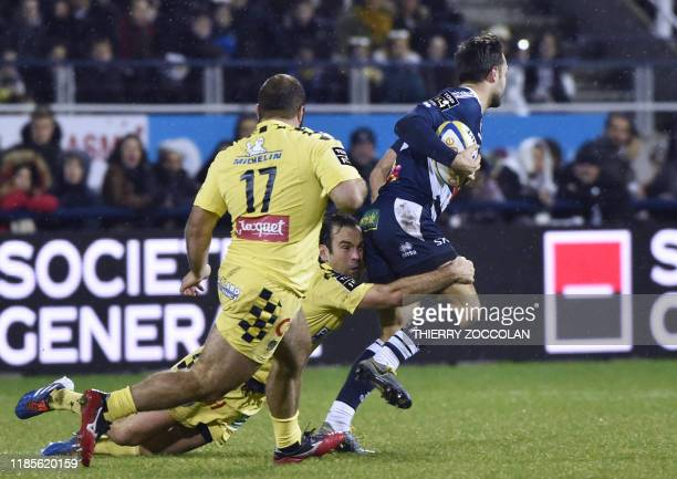 Agen's French fullback Loris Tolot is tackled by Clermont's French scrum-half Morgan Parra during the French Top 14 rugby union match between ASM...