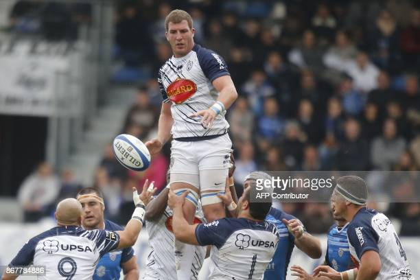 Agen's French lock Denis Marchois passes the ball during the French Top 14 rugby union match between Castres and Agen at the Pierre Fabre Stadium in...