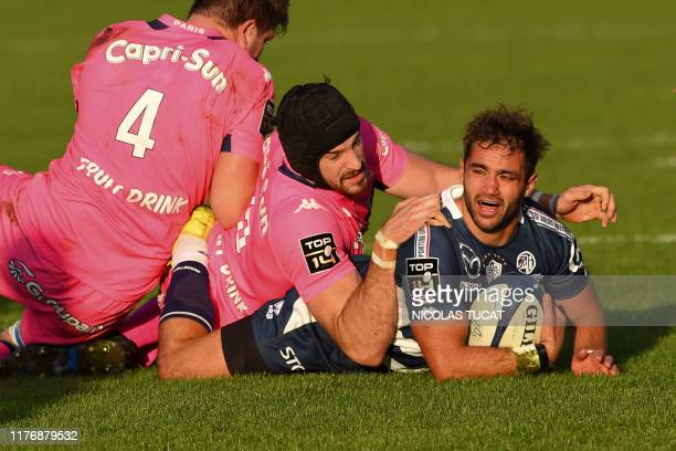 Agen's French scrumhalf Paul Abadie is tackled during the French Top14 rugby union match between Agen and Stade Francais at the Armandie stadium in...