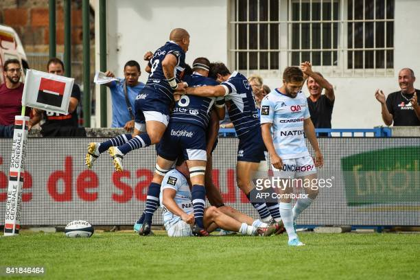 Agen's players celebrate as Racing's Teddy Iribaren looks on after New Zealander wing George Tilsley scored a try during the French Top 14 rugby...