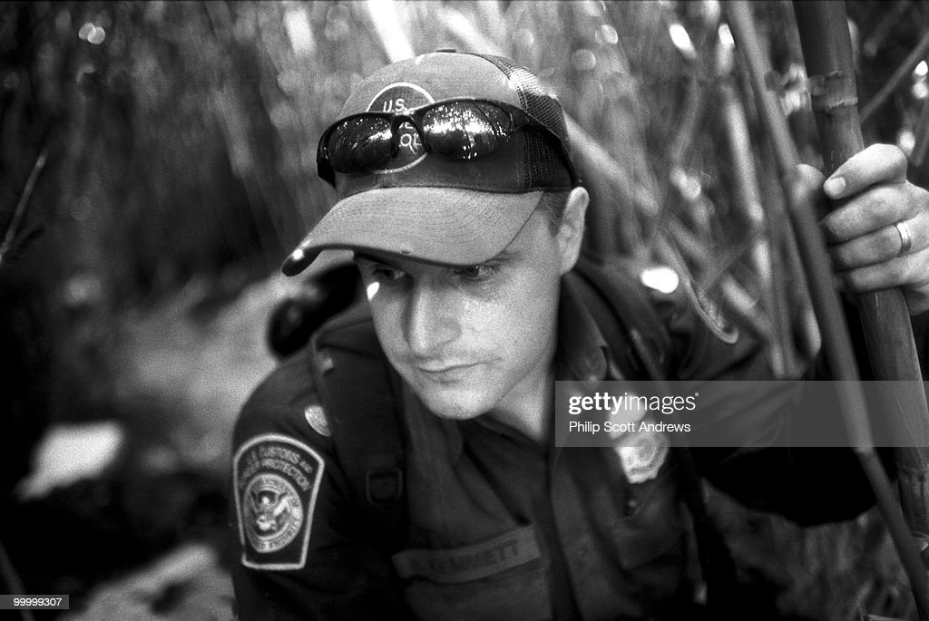 Agent Brian Kemmett crouches among the rieds beside the Rio Grande. 'They build these tunnel's and when we find them they cut new ones, it's a game of cat and mouse.'