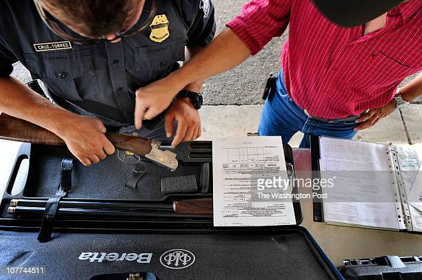 Agent checks a gun and ammo with its owner who is headed into Mexico at the Port of Entry in Laredo, TX July 27, 2010. US Border Patrol, ICE and...