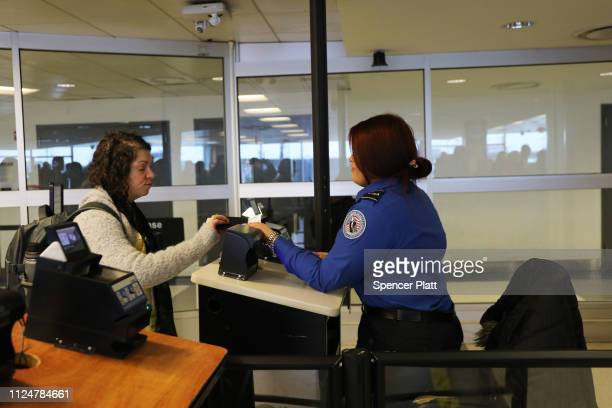 TSA agent checks a passengers documents on a security screening line at LaGuardia Airport after the Federal Aviation Administration announced it is...