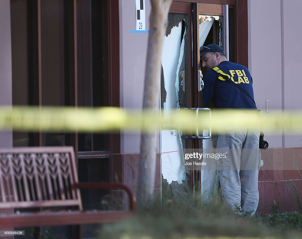 A FBI agent is seen next to a broken out glass door on the building at the Inland Regional Center were 14 people were killed on December 7, 2015 in San Bernardino, California. FBI and other law enforcement officials continue to investigate the mass shooting at the Inland Regional Center in San Bernardino that left 14 people dead and another 21 injured on December 2nd.