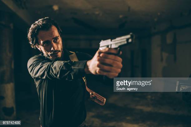 agent man holding hand gun - shooting crime stock pictures, royalty-free photos & images