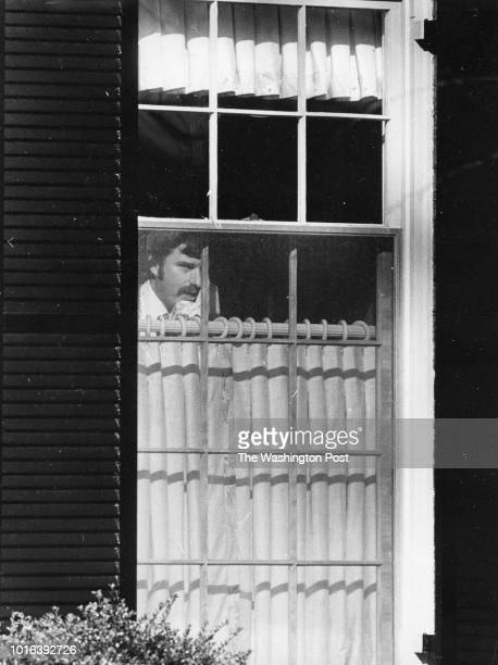 Agent peeps out the window yesterday at reporters watching Lee Lescaze's house on February 3 1980