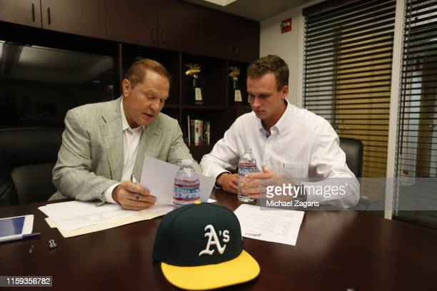 Agent Scott Boras looks goes over Oakland Athletics first round pick Logan Davidson contact in the office prior to the game between the Athletics and...