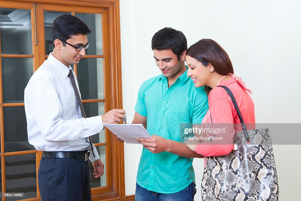 Agent selling property to young couple : Stock Photo