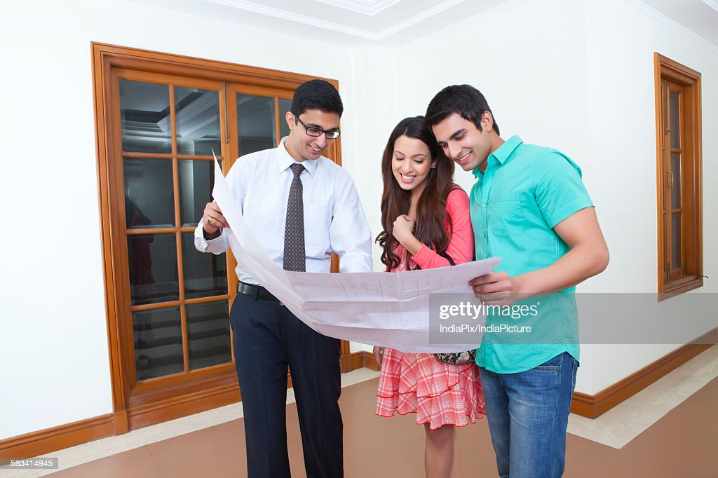 Agent showing property to young couple : Stock Photo