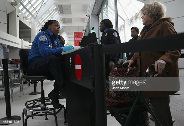 TSA agent speaks with a traveler at a special TSA Precheck lane at Terminal C of the LaGuardia Airport on January 27 2014 in New York City Once...