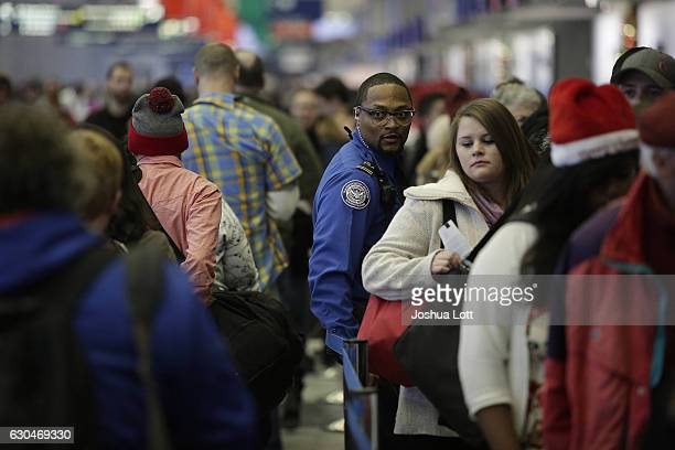 TSA agent stands with travelers in the TSA security line at O'Hare International Airport on December 23 2016 in Chicago Illinois O'hare International...